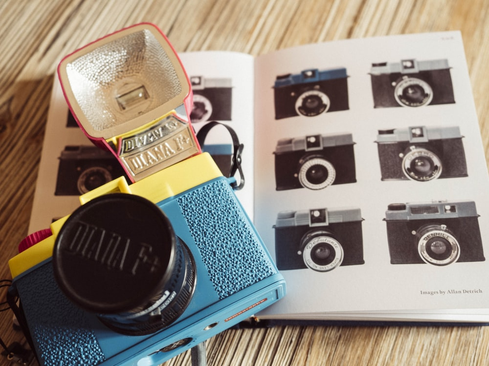 blue and black DSLR camera on white open book