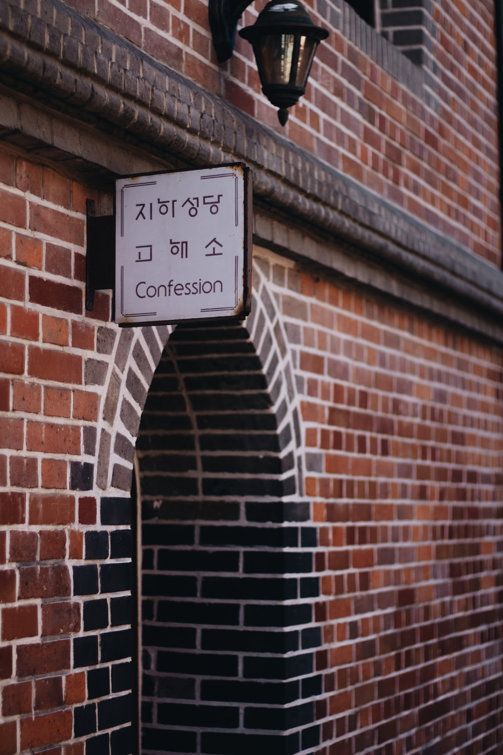 Confession signage beside brown concrete wall