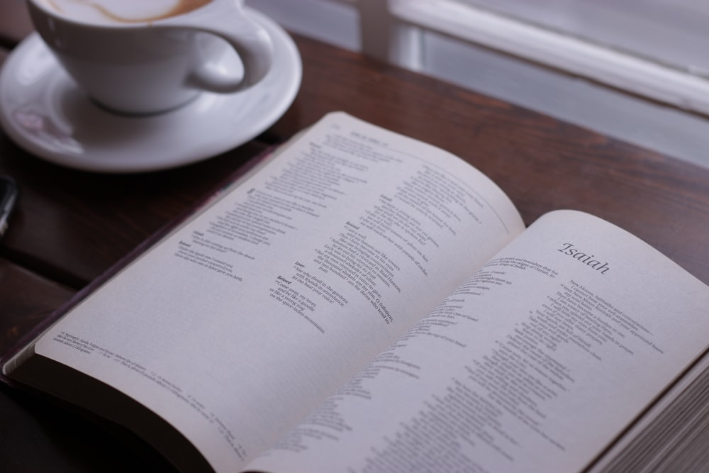 open Bible in showing Isaiah chapter on table near cup of coffee