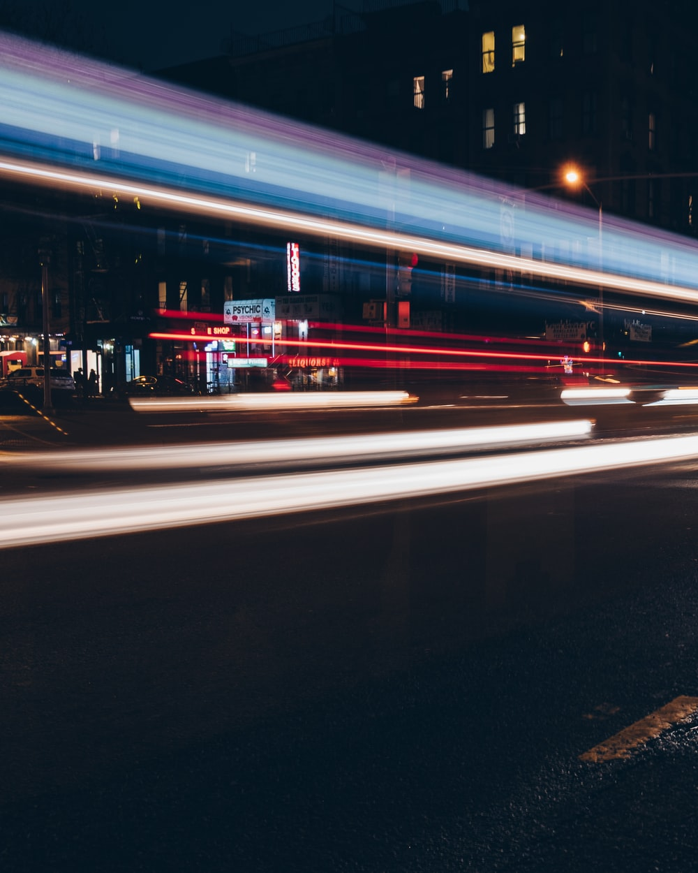 time-lapse photography of vehicle near buildings at night