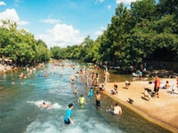 Right behind end fance of Barton Springs pool many locals enjoy refreshing waters of the springs with their dogs. The place is free-for-all. Here you can meet all kinds of people; this photo was taken from Barton Springs pool side in one of the hot Sundays in August.