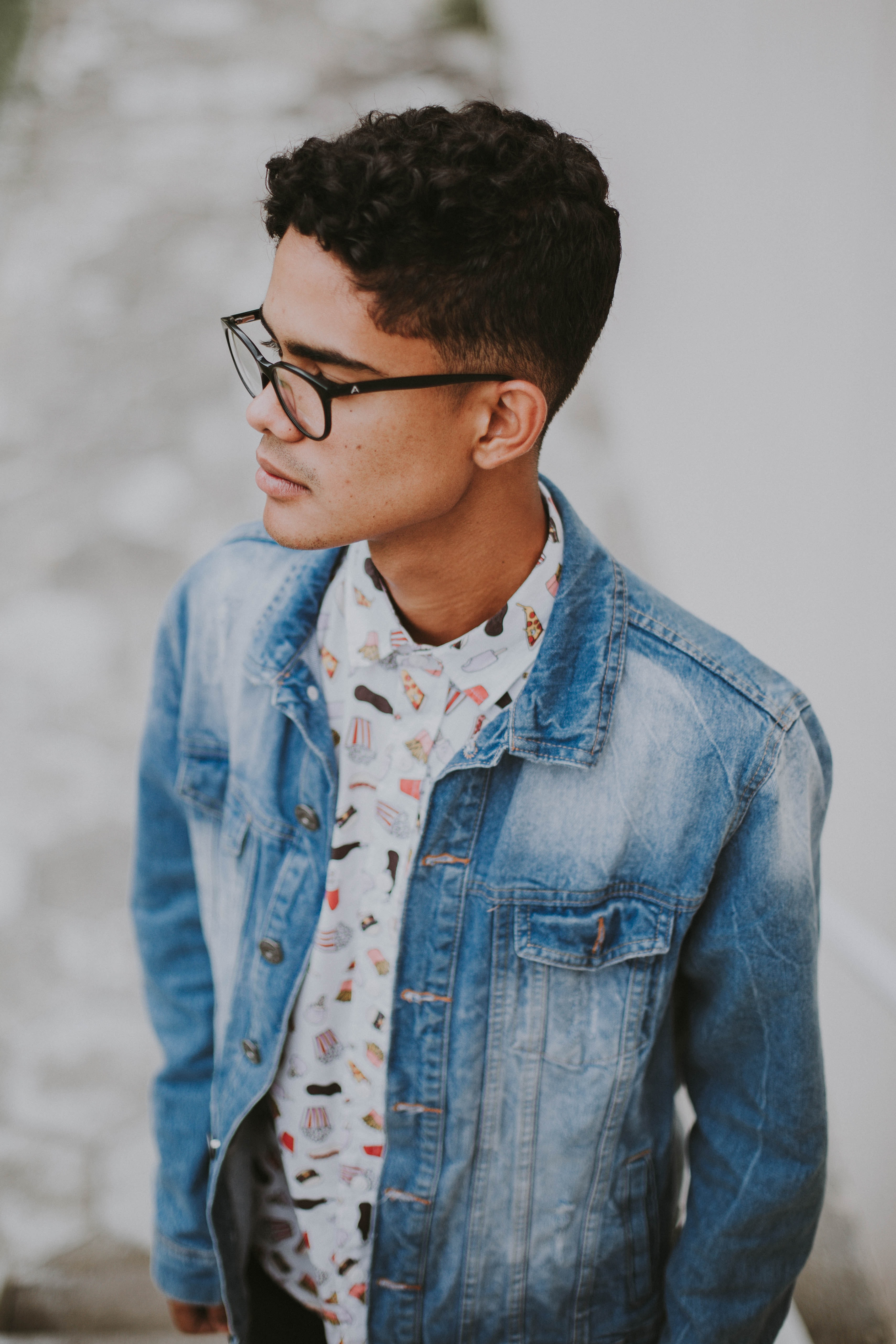 man wearing blue denim jacket looking sideways