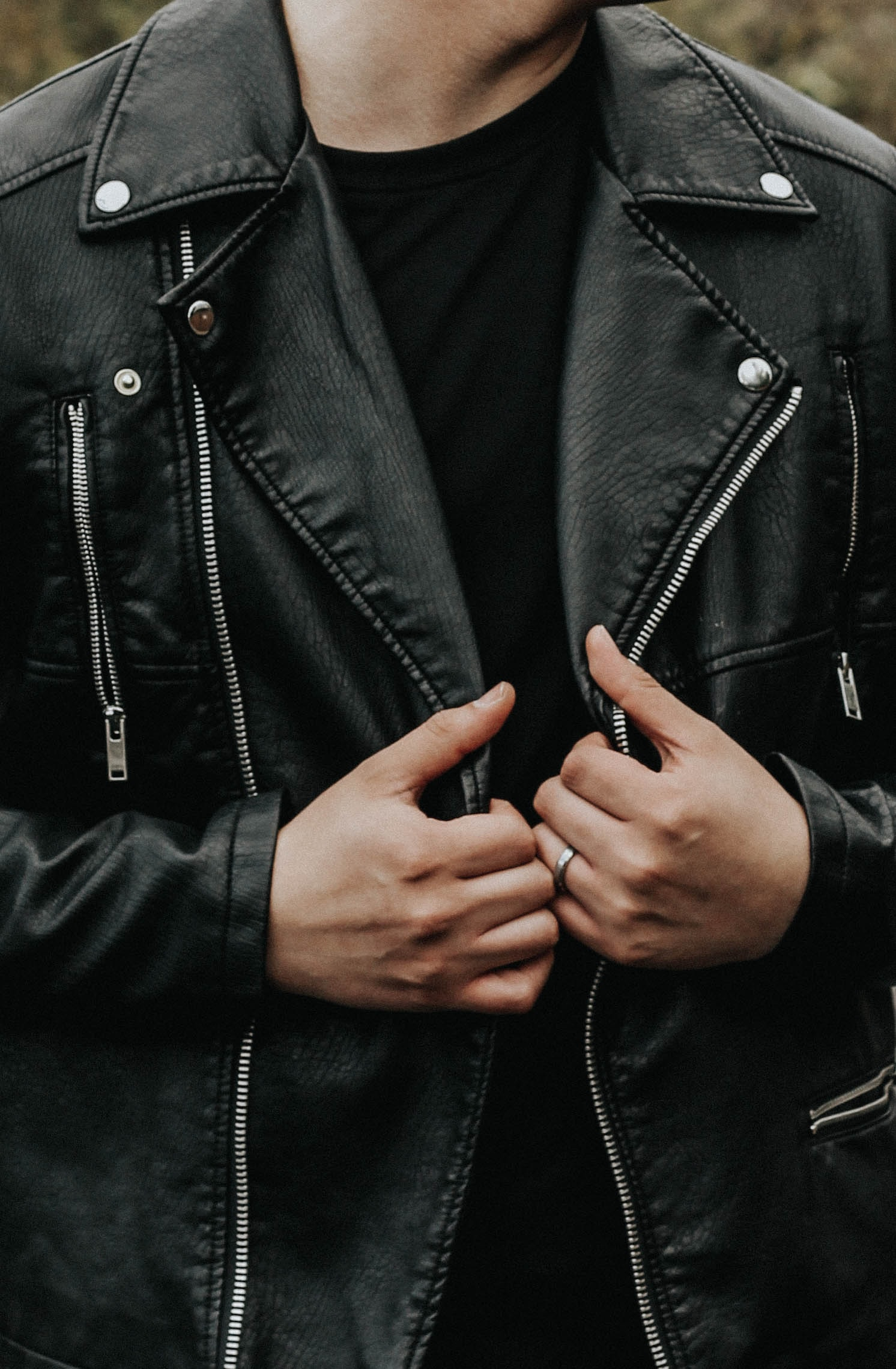 man holding his leather jacket