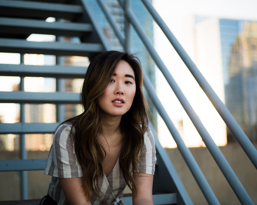woman sitting on white metal stairs