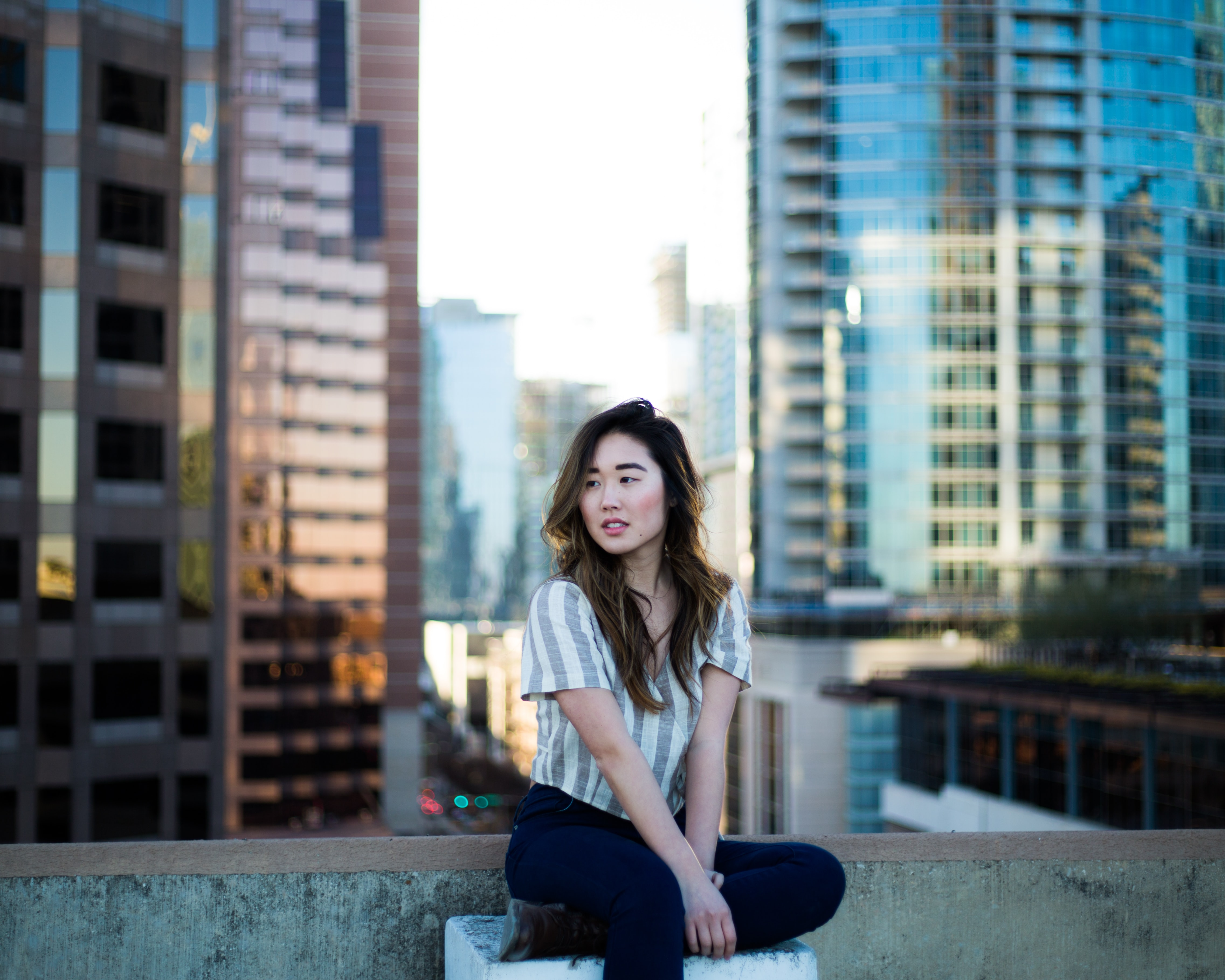 selective focus photography of woman in gray shirt sitting near building edge
