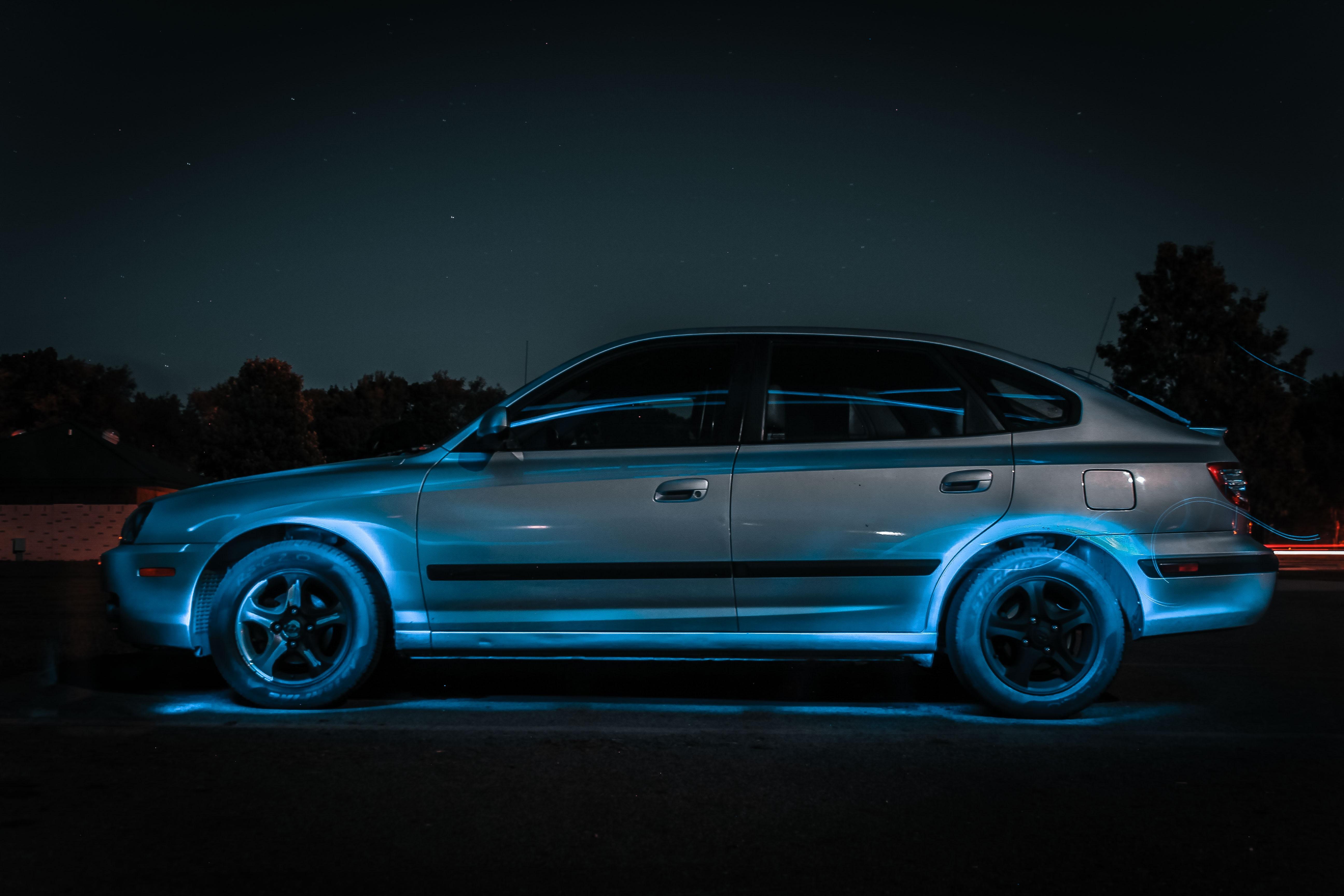 silver sedan park on road with blue lights