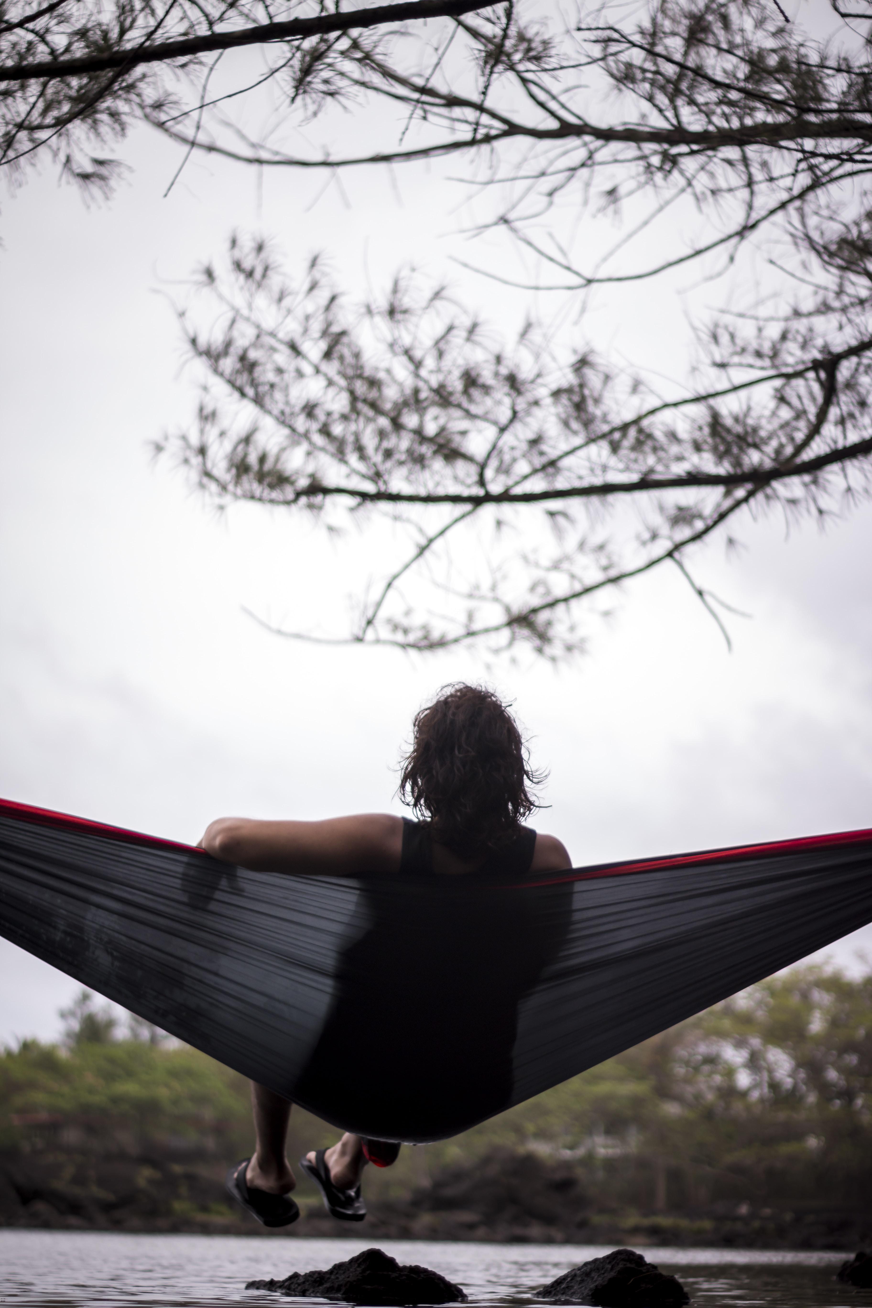 woman sitting on hammock facing body of water