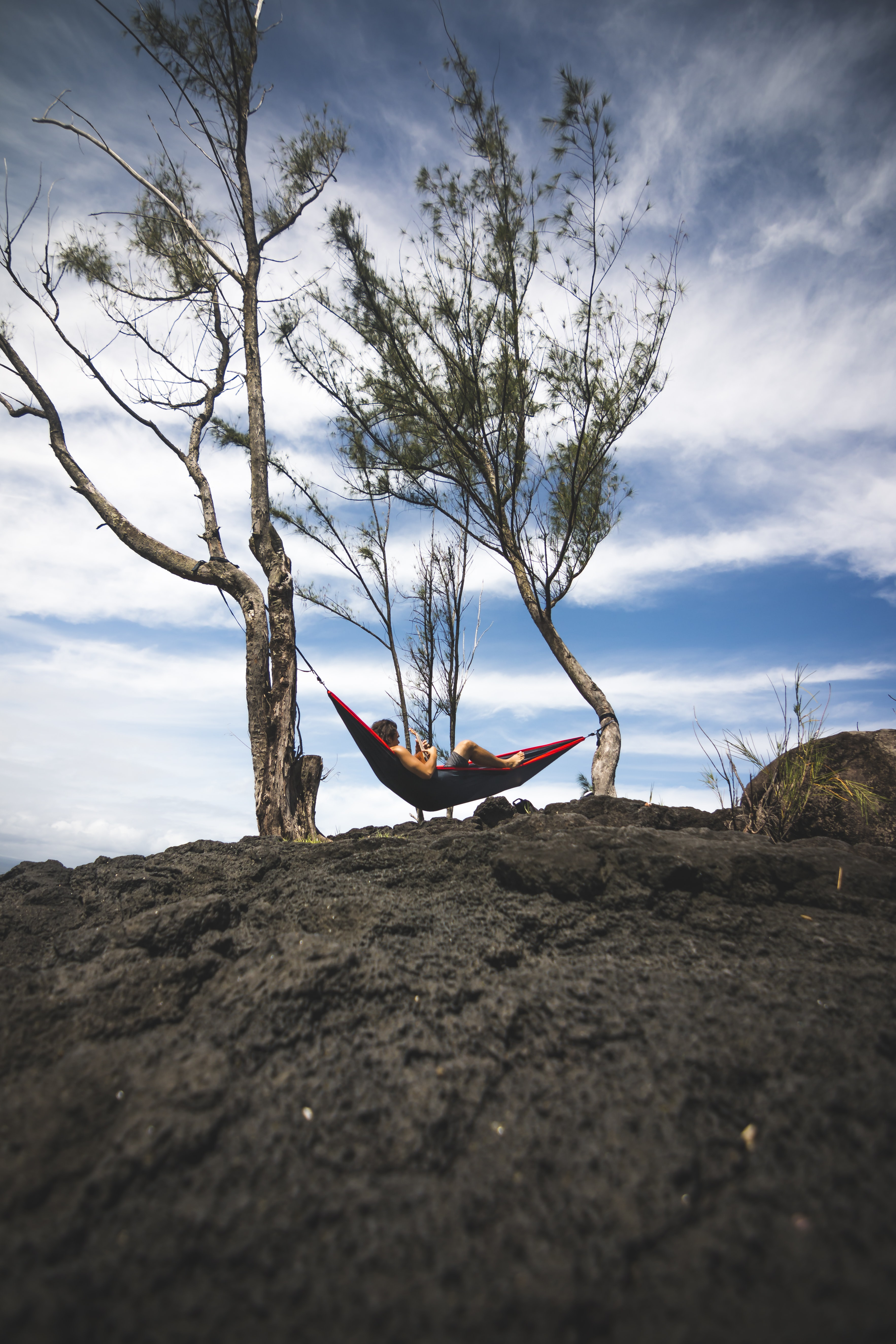 person lying on black and red hammock during daytime