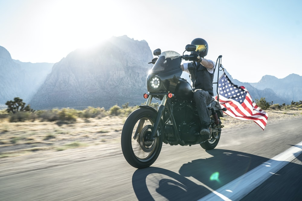 fanning photography of man riding cruiser motorcycle near mountain