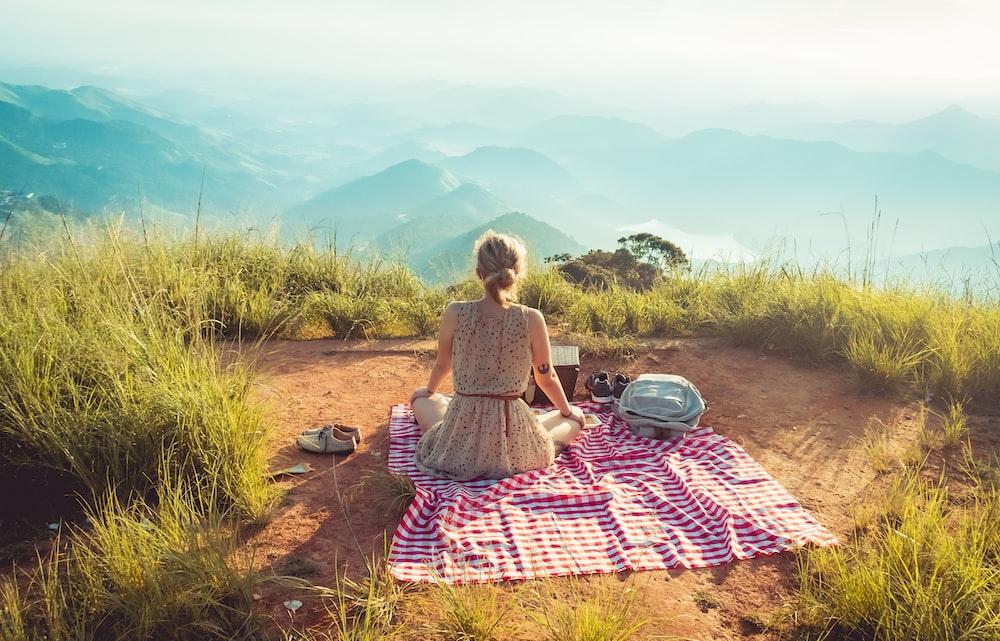 woman wearing gray sleeveless dress sitting on the picnic mat