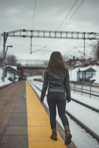 woman walking beside the railway