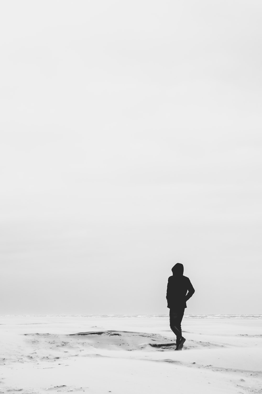 man wearing hoodie standing on snow covered field during daytime