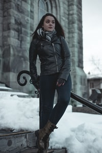 woman leaning on black metal railing during daytime