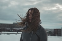 woman standing while hair is blown by wind