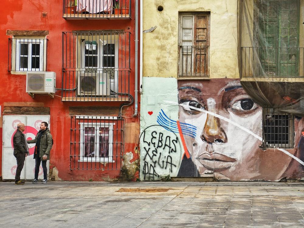 two persons talking beside graffiti