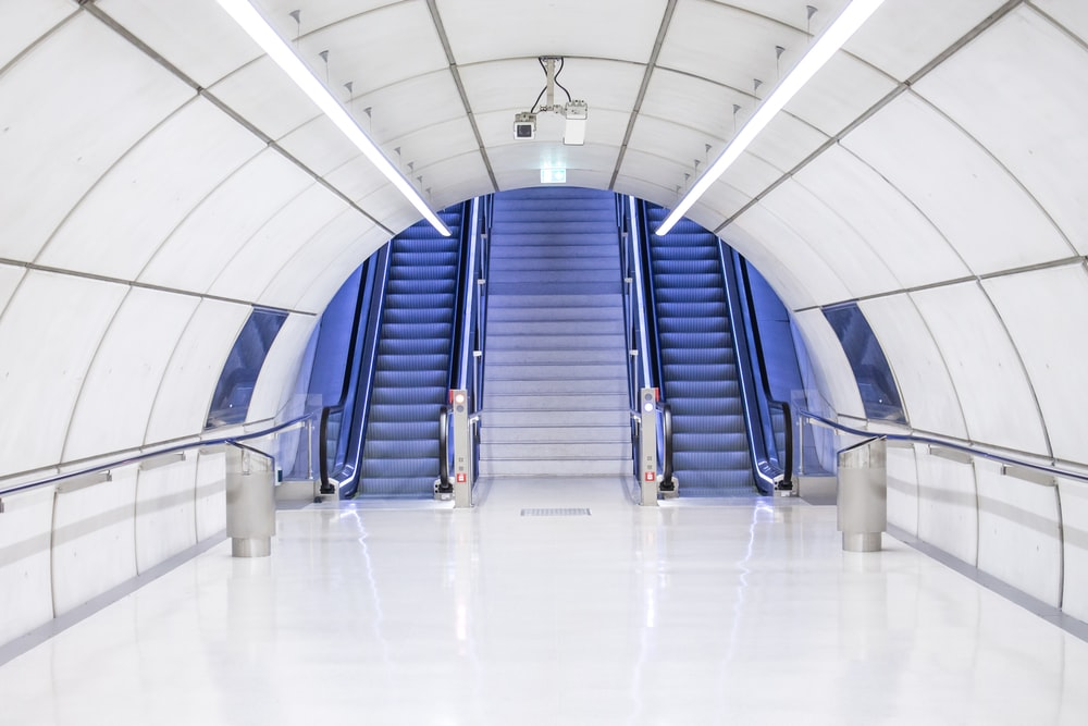 gray concrete arch hallway near escalator