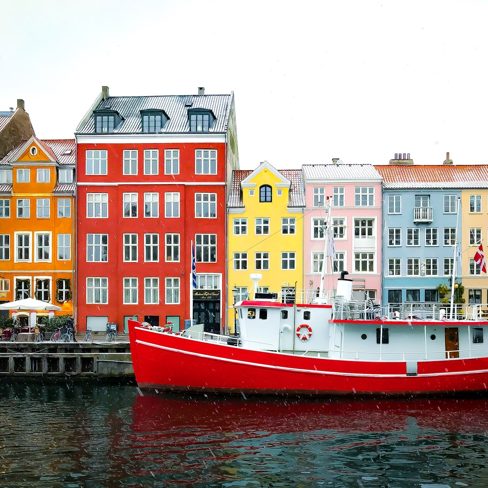 assorted-color buildings near red boat docked on port during daytime
