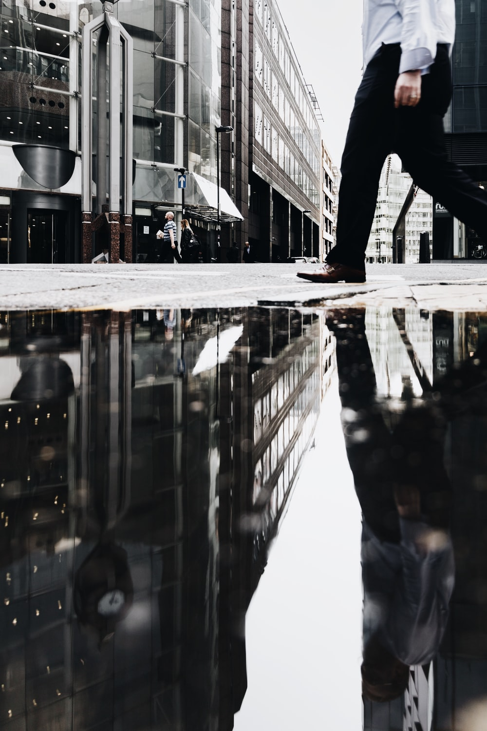 man walking near puddle of water casting reflection