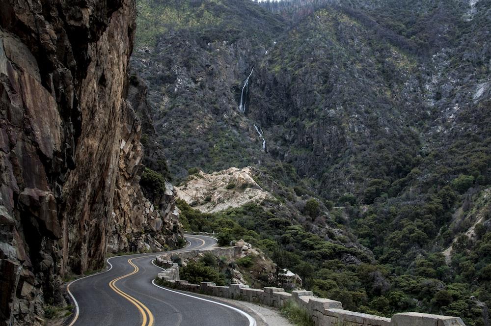 asphalt road beside cliff
