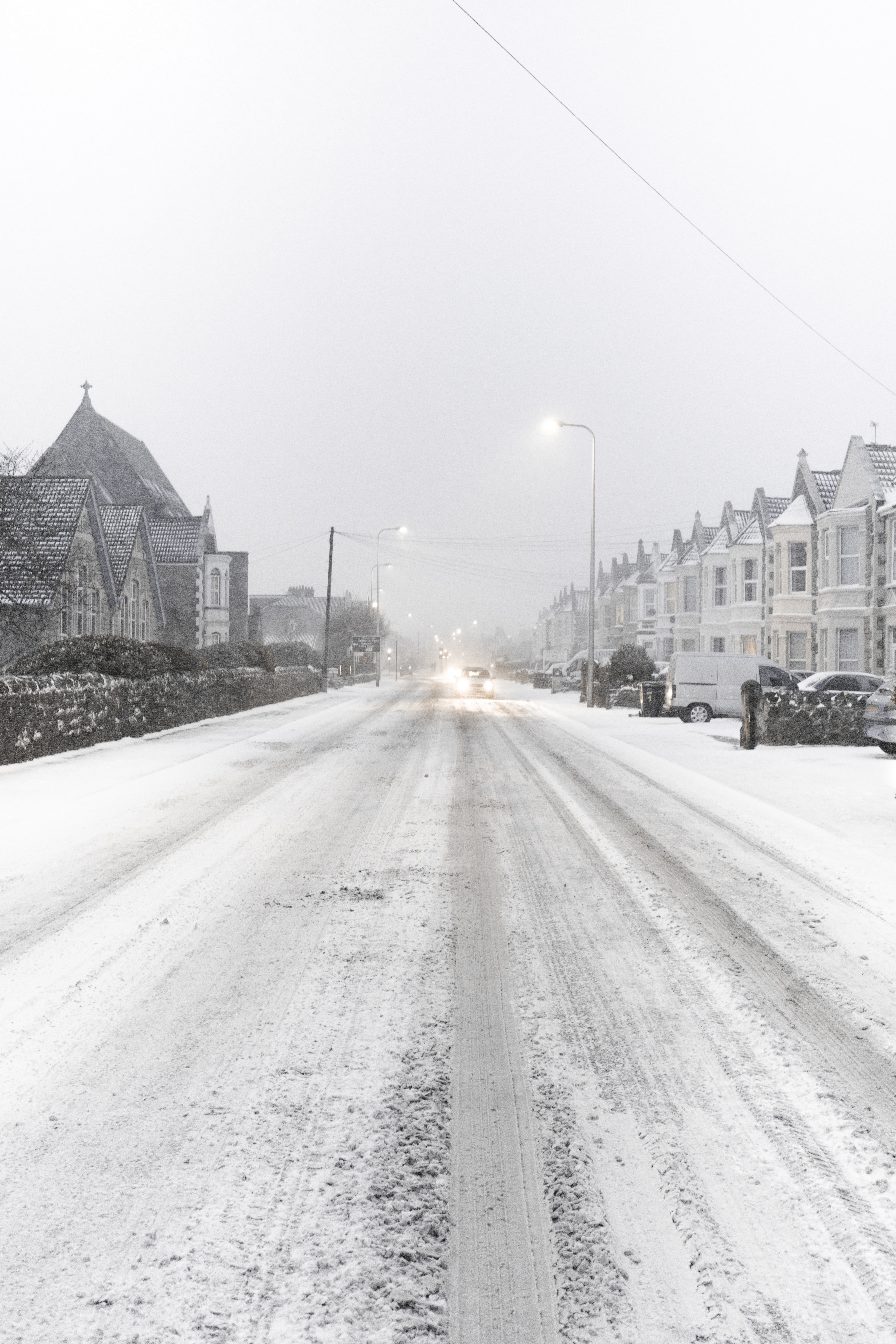 snow covered road between village and vehicles