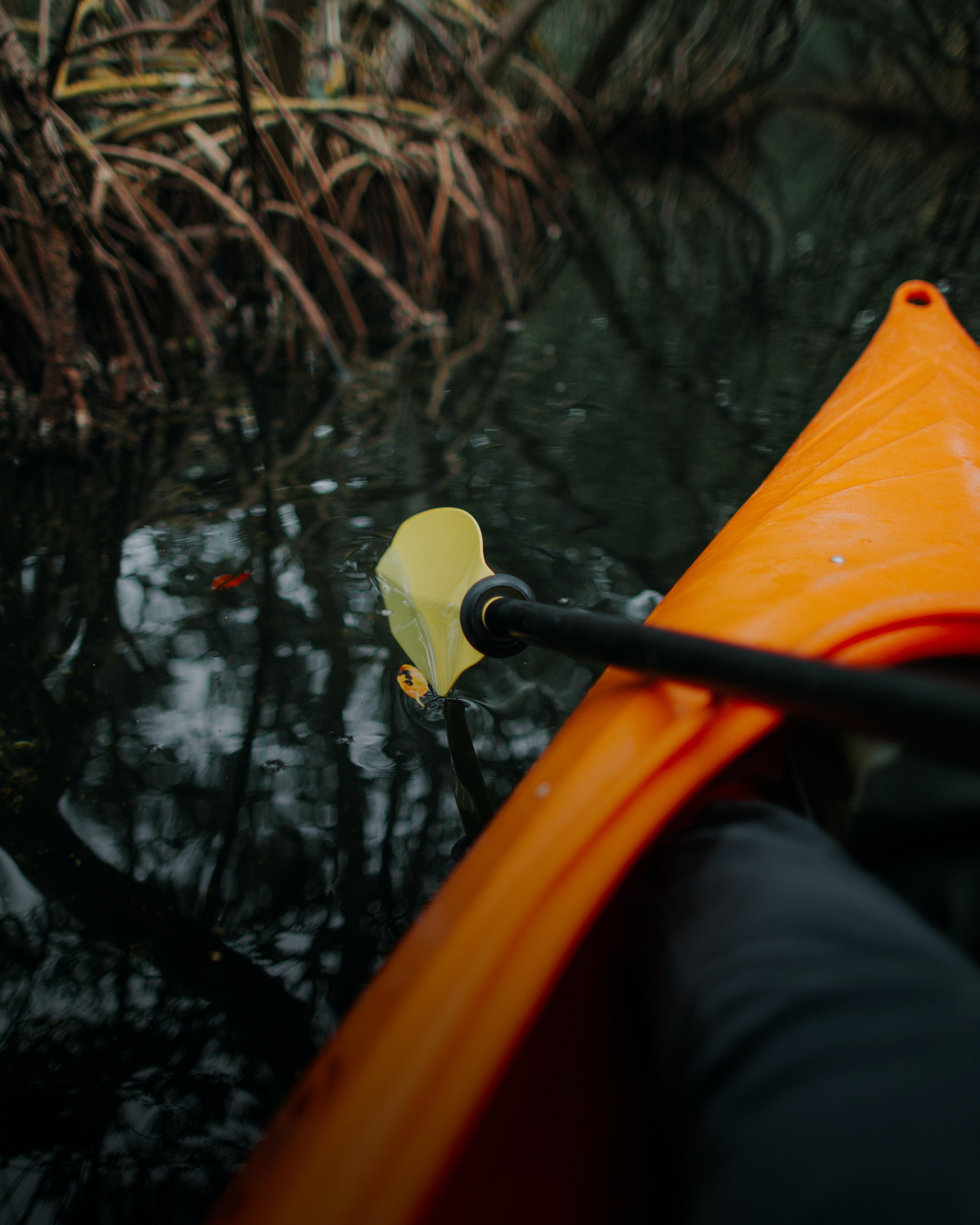 person riding orange kayak