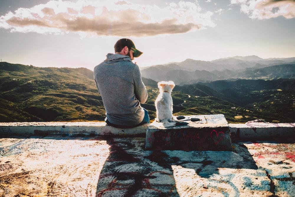 man sitting beside dog