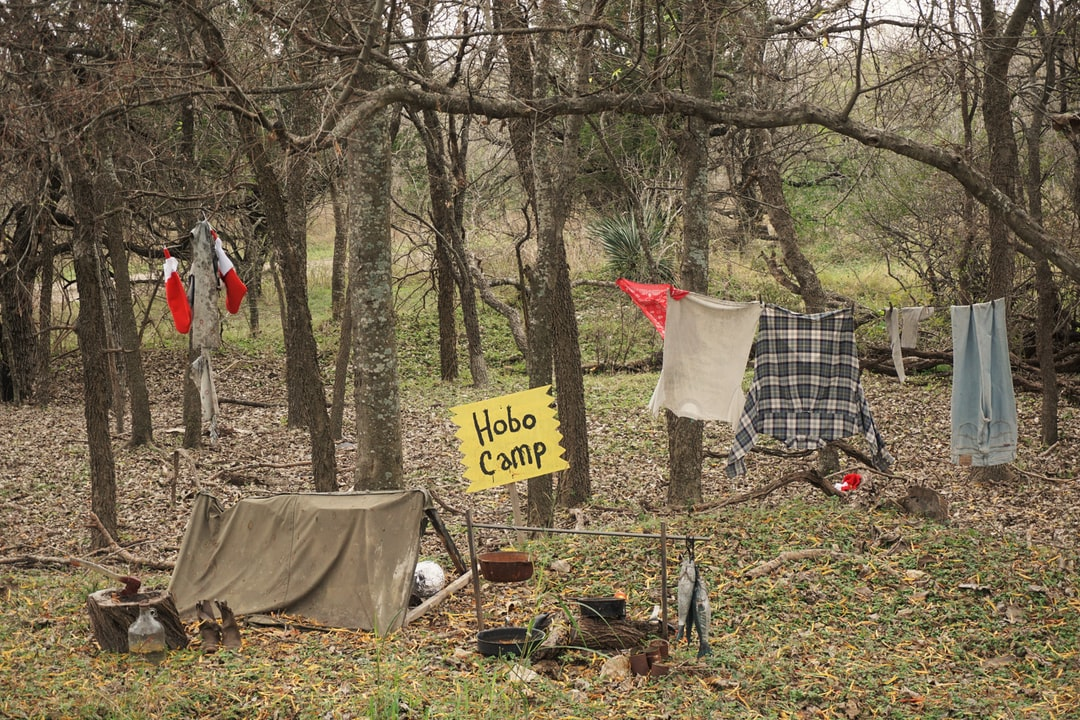 On a cold December day, near the Texas Transportation Museum, en route to San Antonio stumbled across this camp in the woods in festive spirit with clothes drying, an axe, fish for supper, pots, pans and tent for a roof.