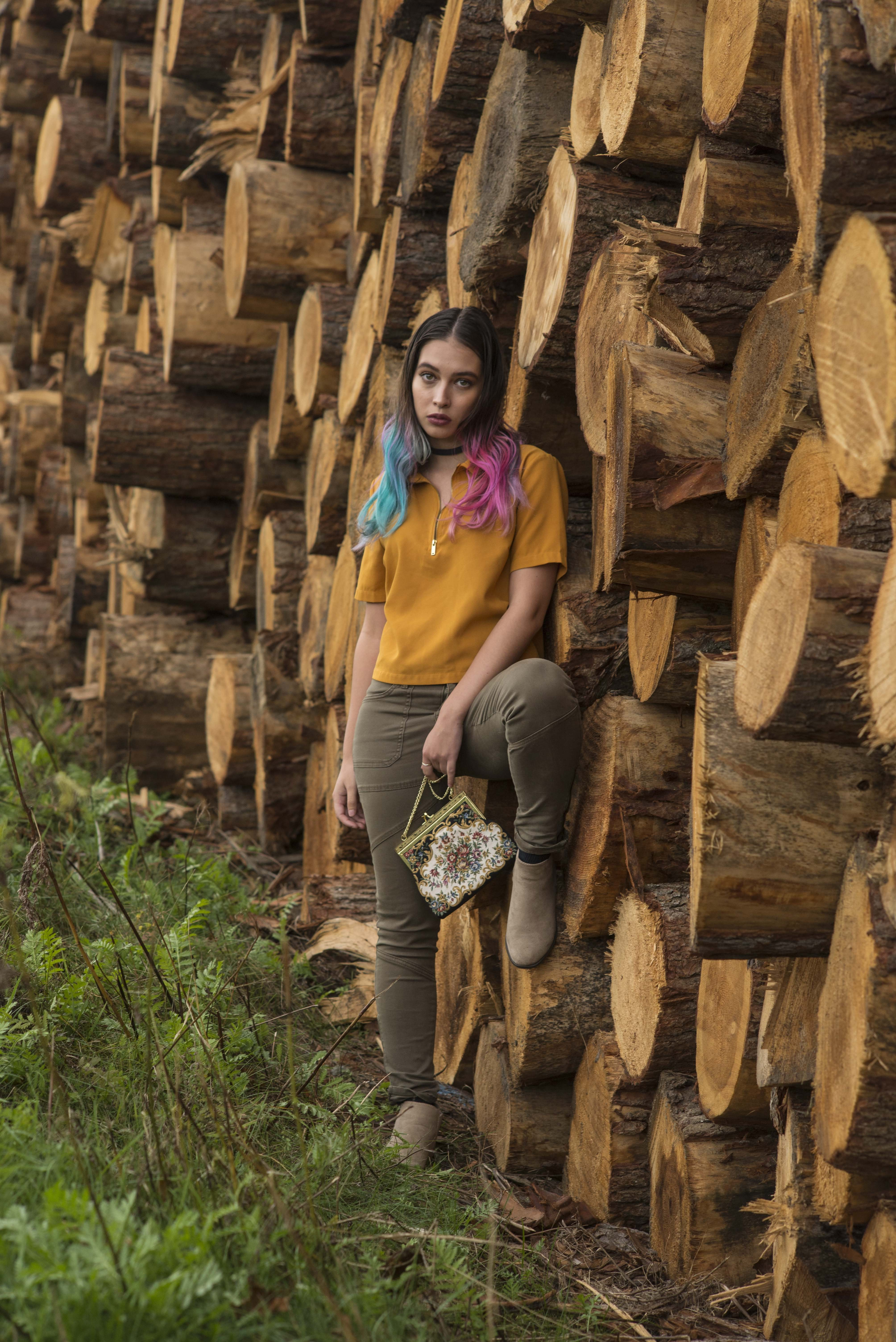 woman standing beside tree logs