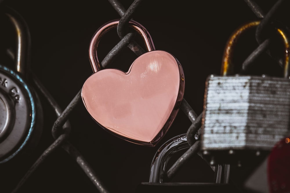 photo of heart-shaped padlock on chain-link fence
