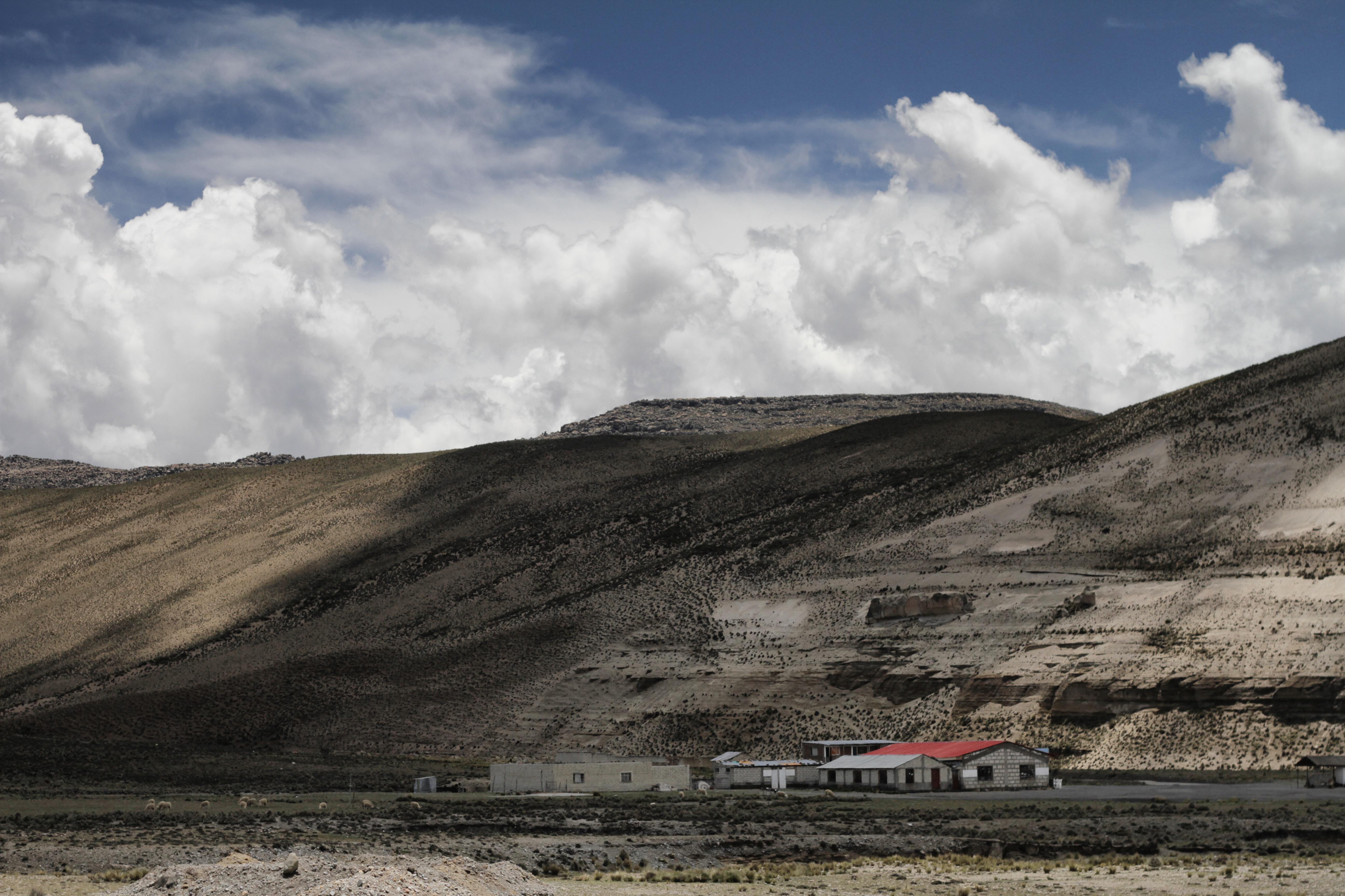 white concrete house near mountains under white clouds