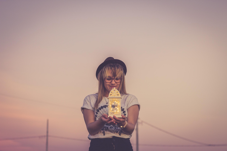 woman holding white candle lantern