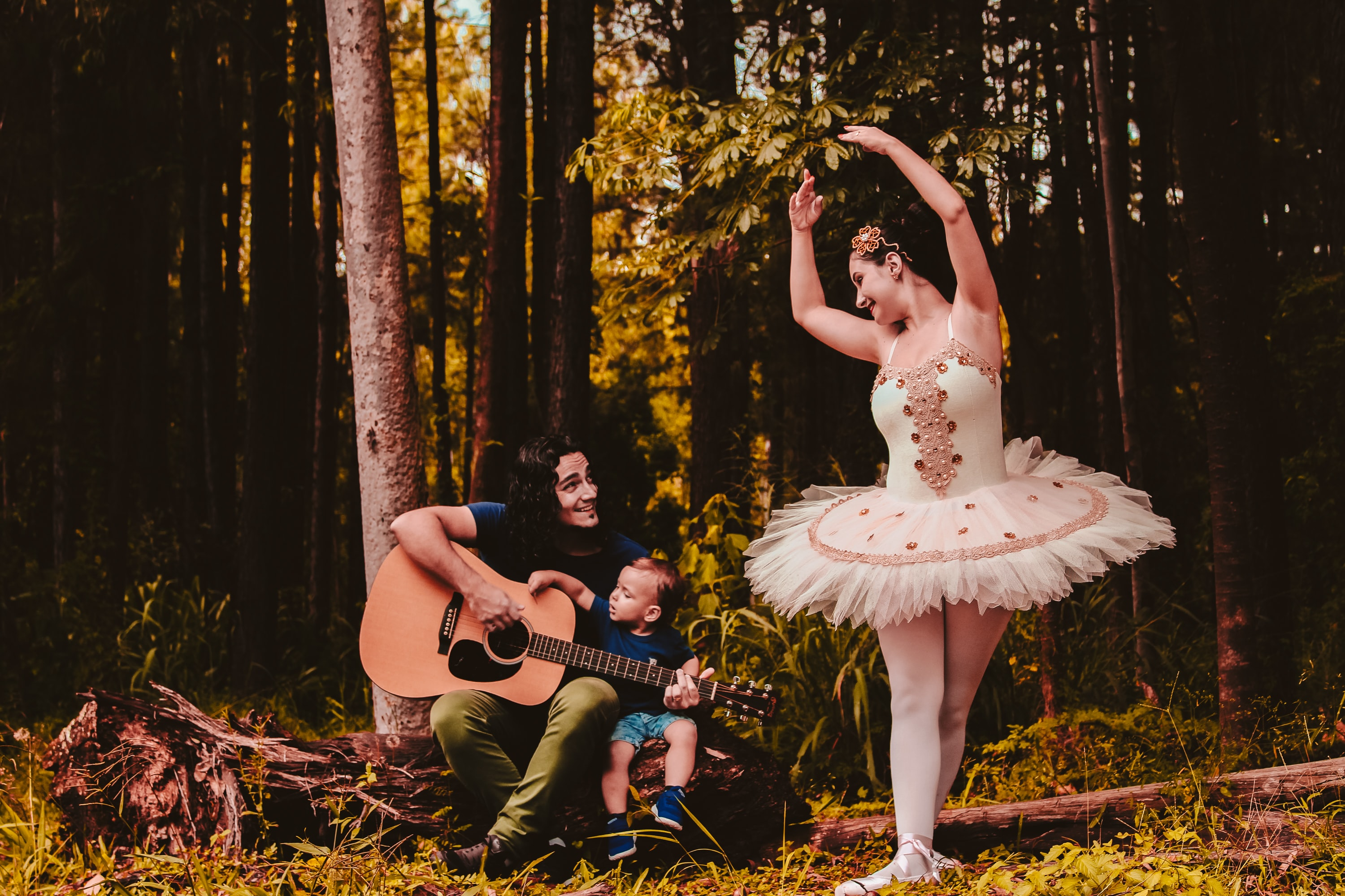 man sitting beside toddler boy while playing guitar and looking at the woman in ballerina dress in the woods