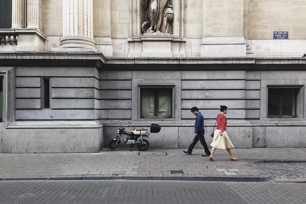 man walking passing trough woman wearing red top