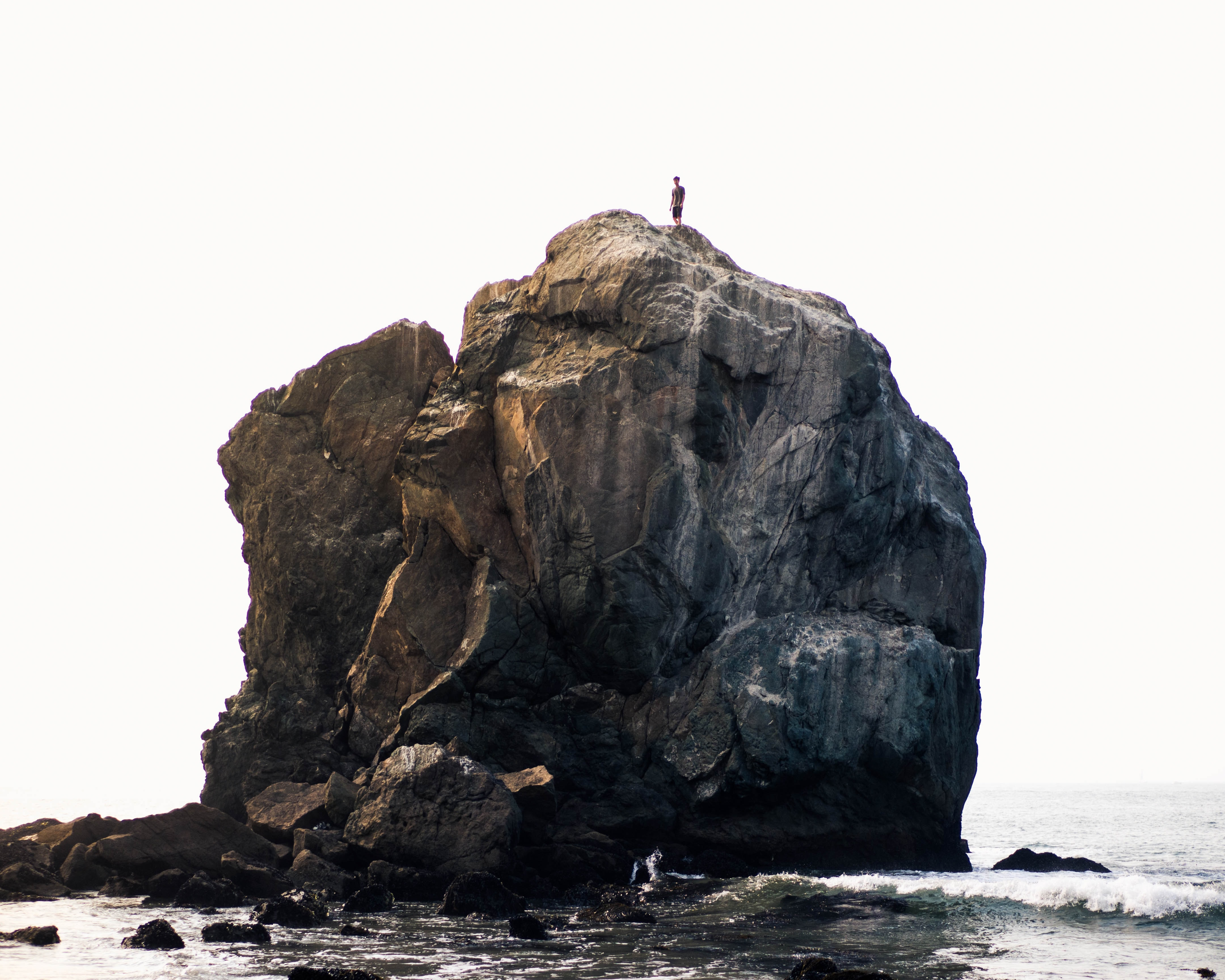 person standing on rock near ocean during daytime