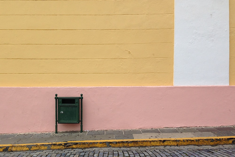 green mailbox beside the pink wall