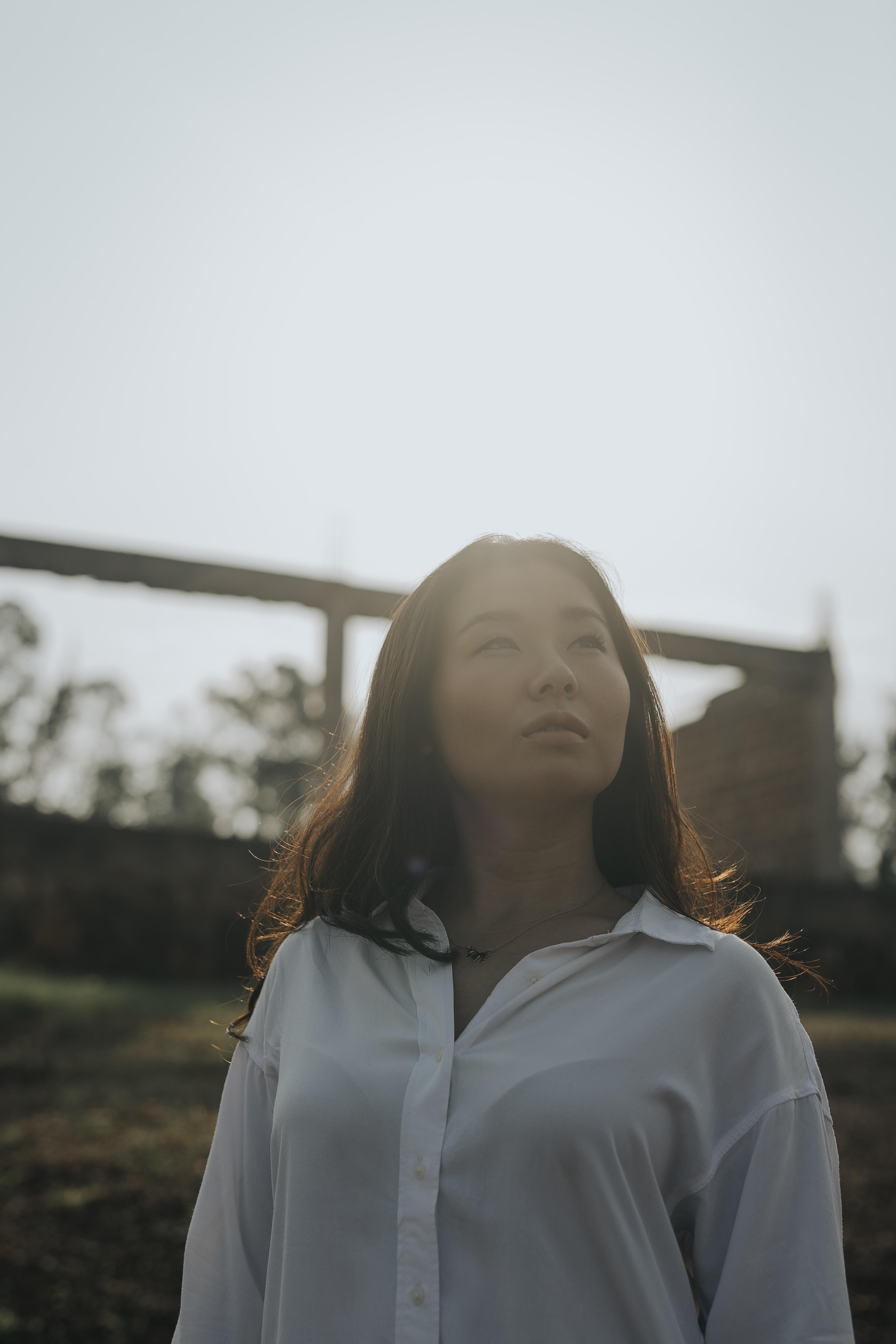 woman wearing white dress shirt looking up