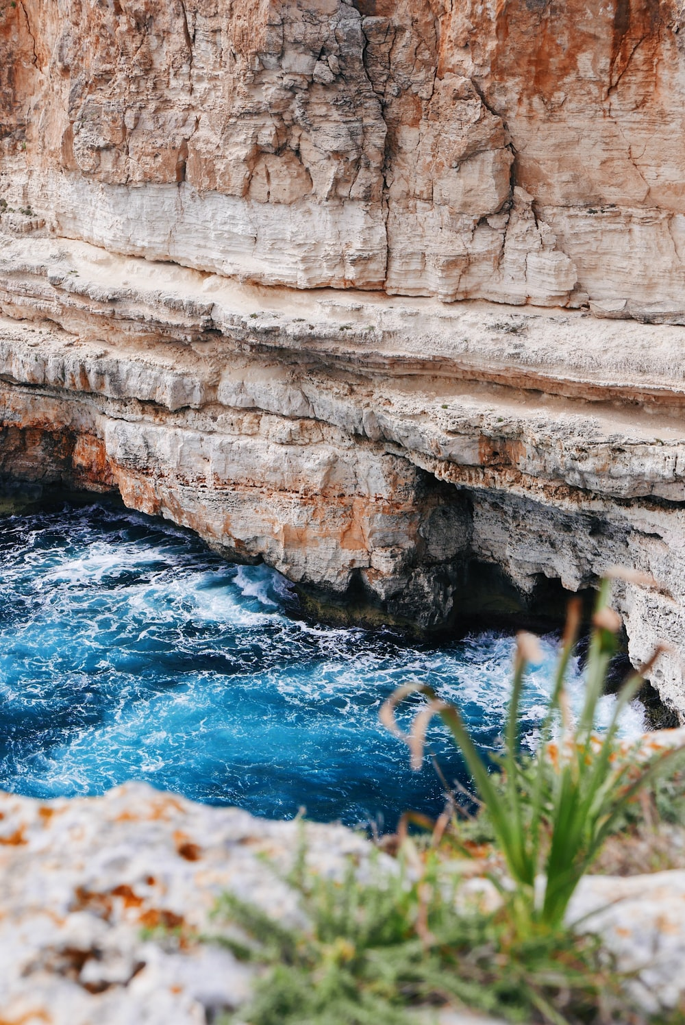 body of water near mountain cliff