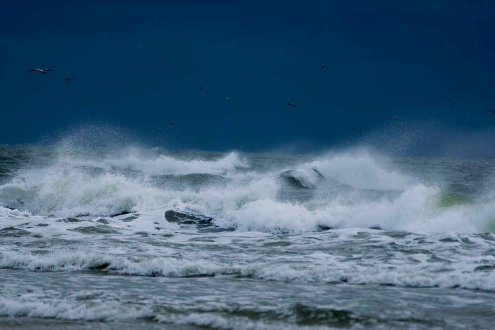 photo of sea waves rushing in to the shore
