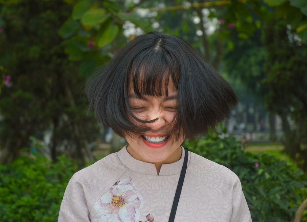 woman smiling closing eyes while flipping her hair