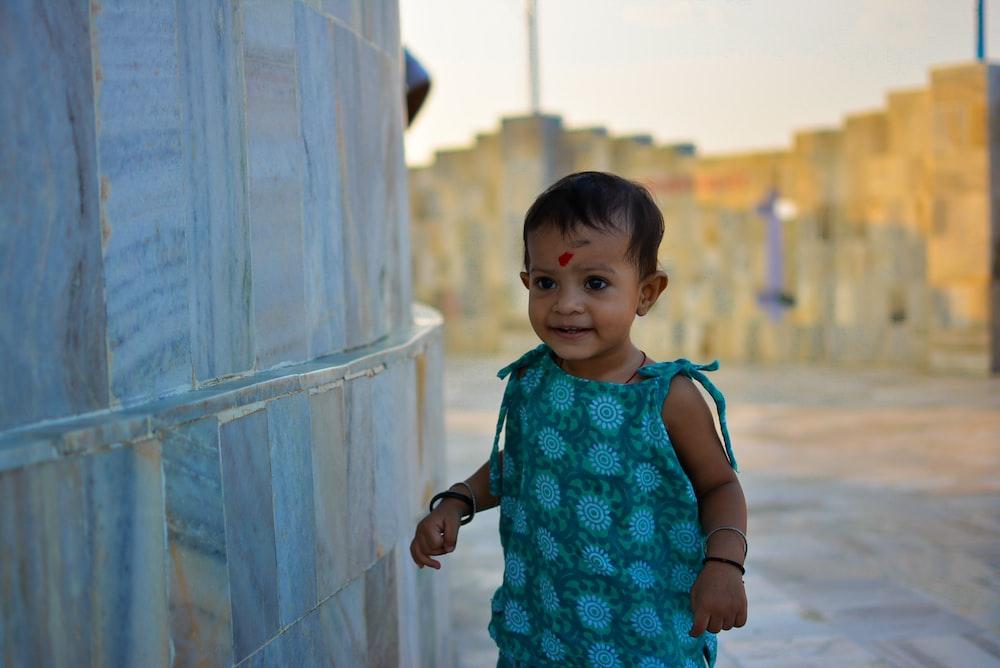 girl standing beside gray tile wall