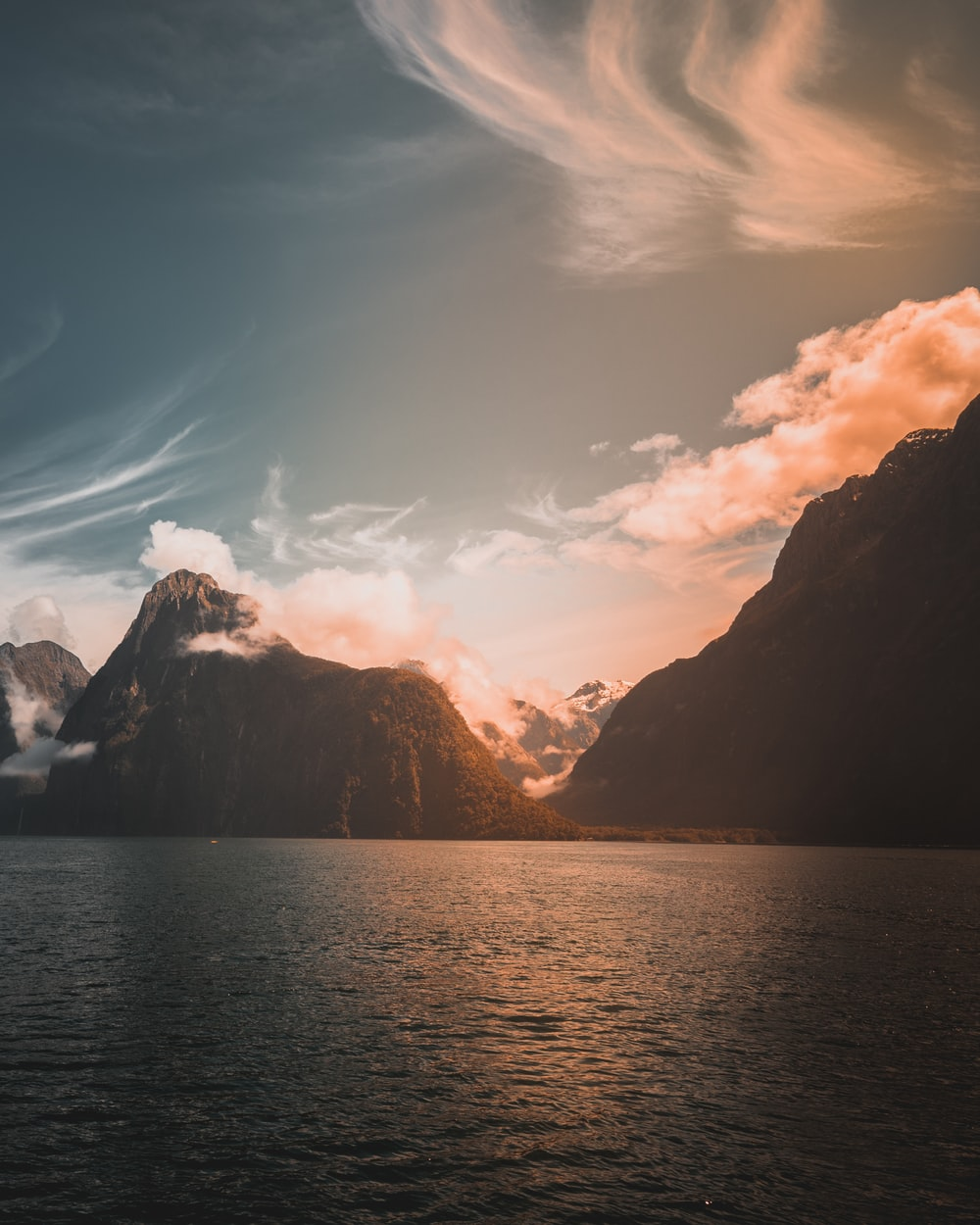 mountains near body of water during golden time