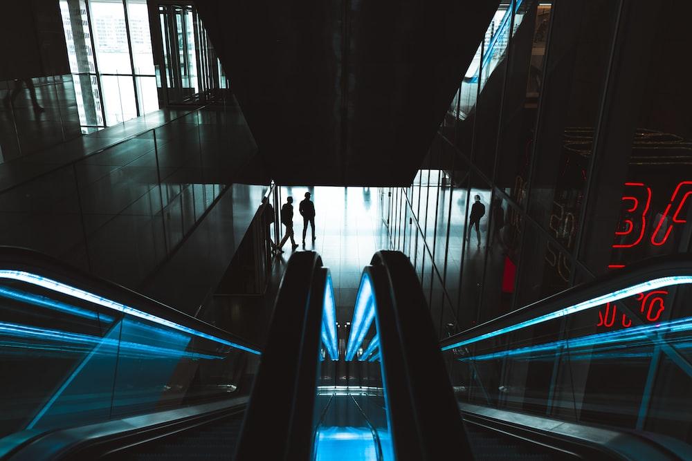 person standing near empty escalator