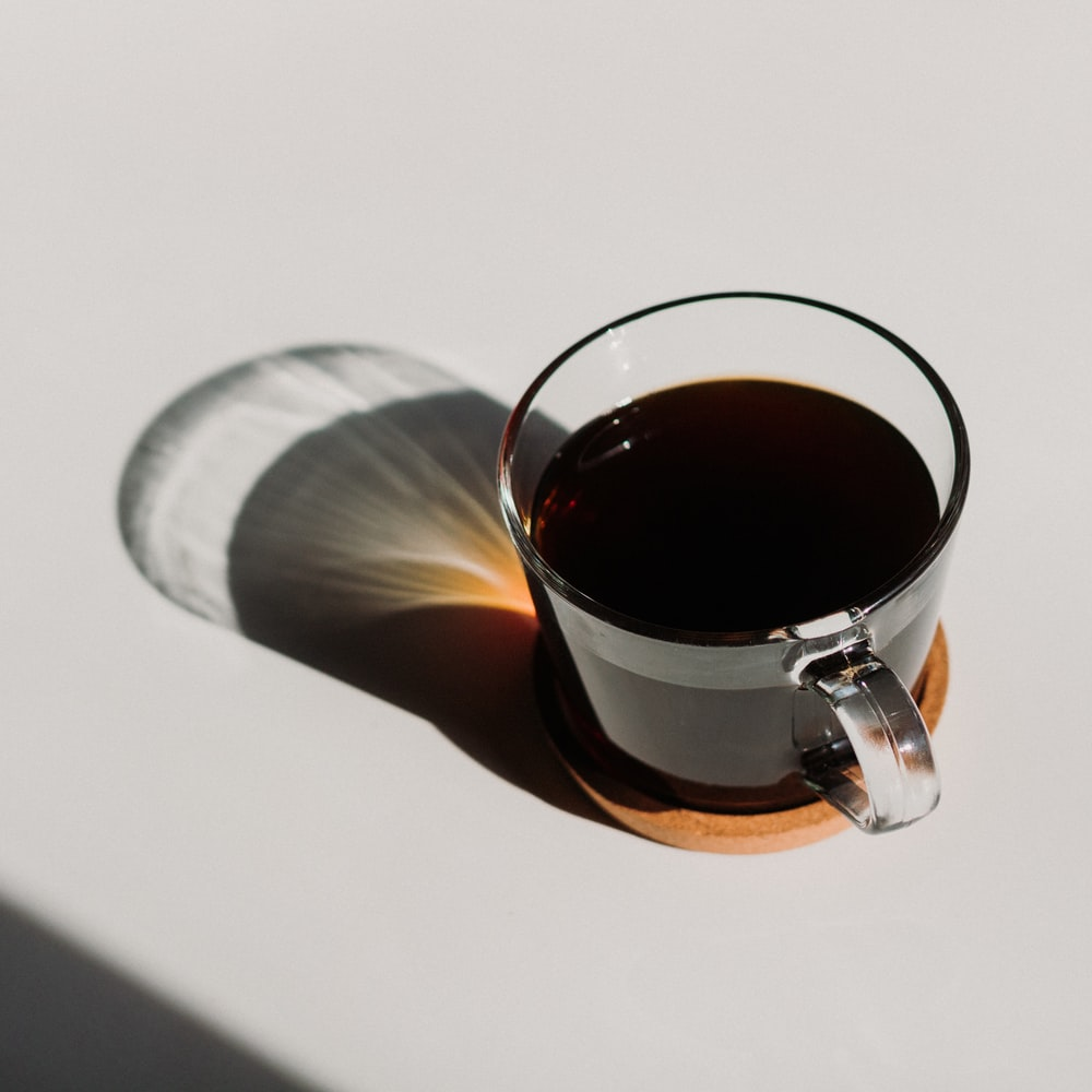 clear glass mug filled with brown liquid
