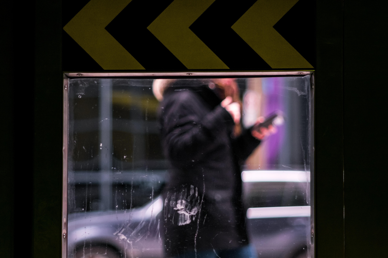 man using smartphone while wearing black jacket