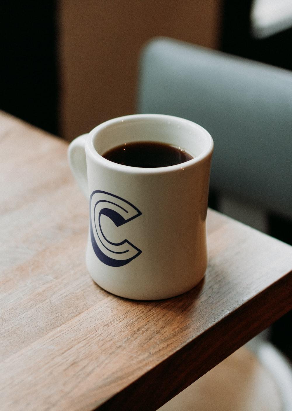 white ceramic mug with black liquid on table