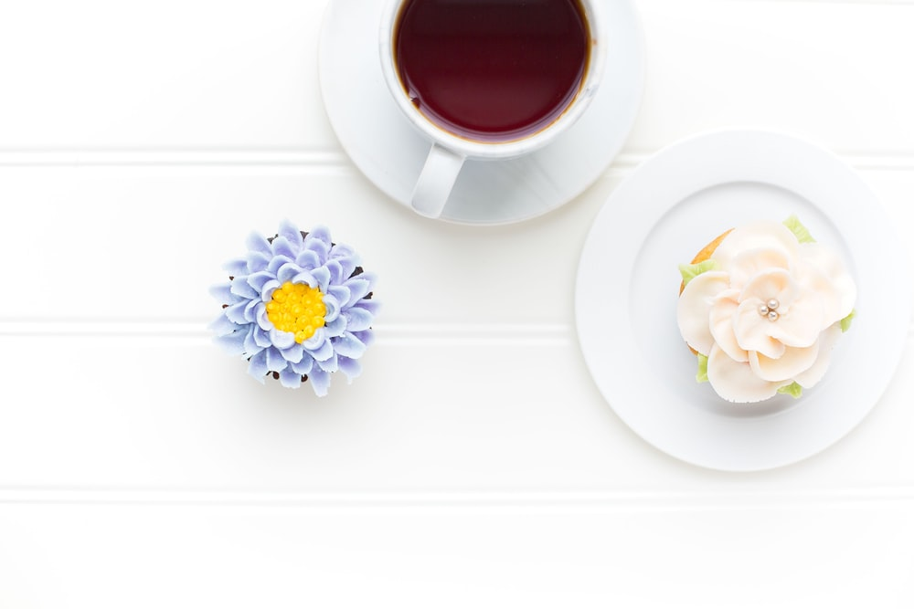 flat lay photography of white coffee cup on white saucer plate and purple flowers