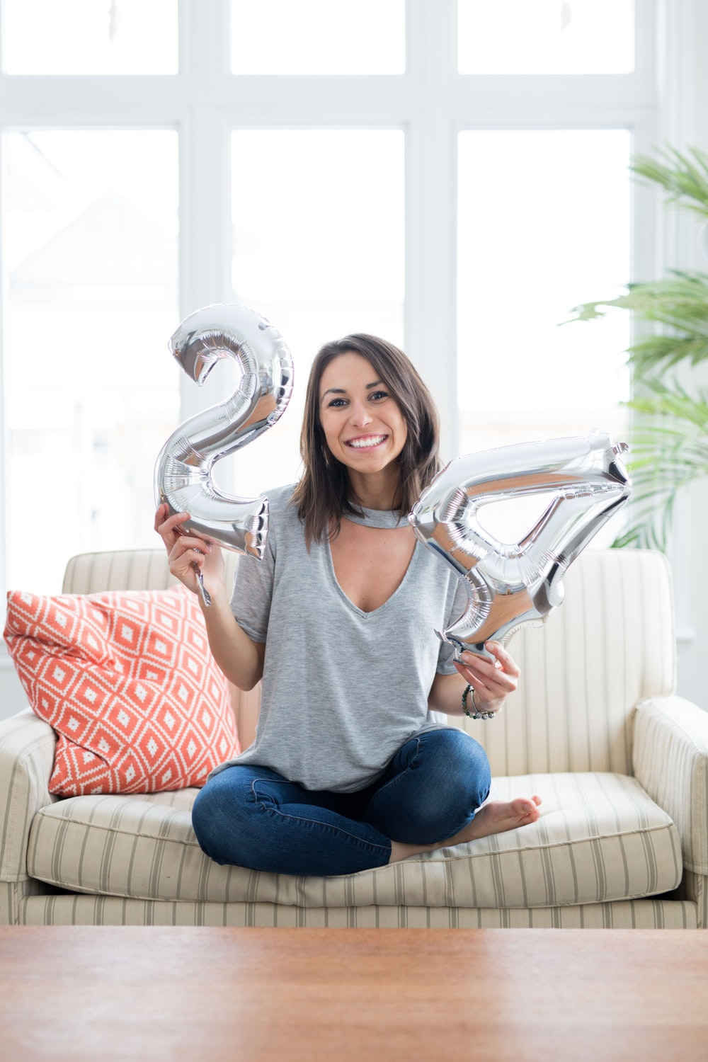 woman holding silver number balloons