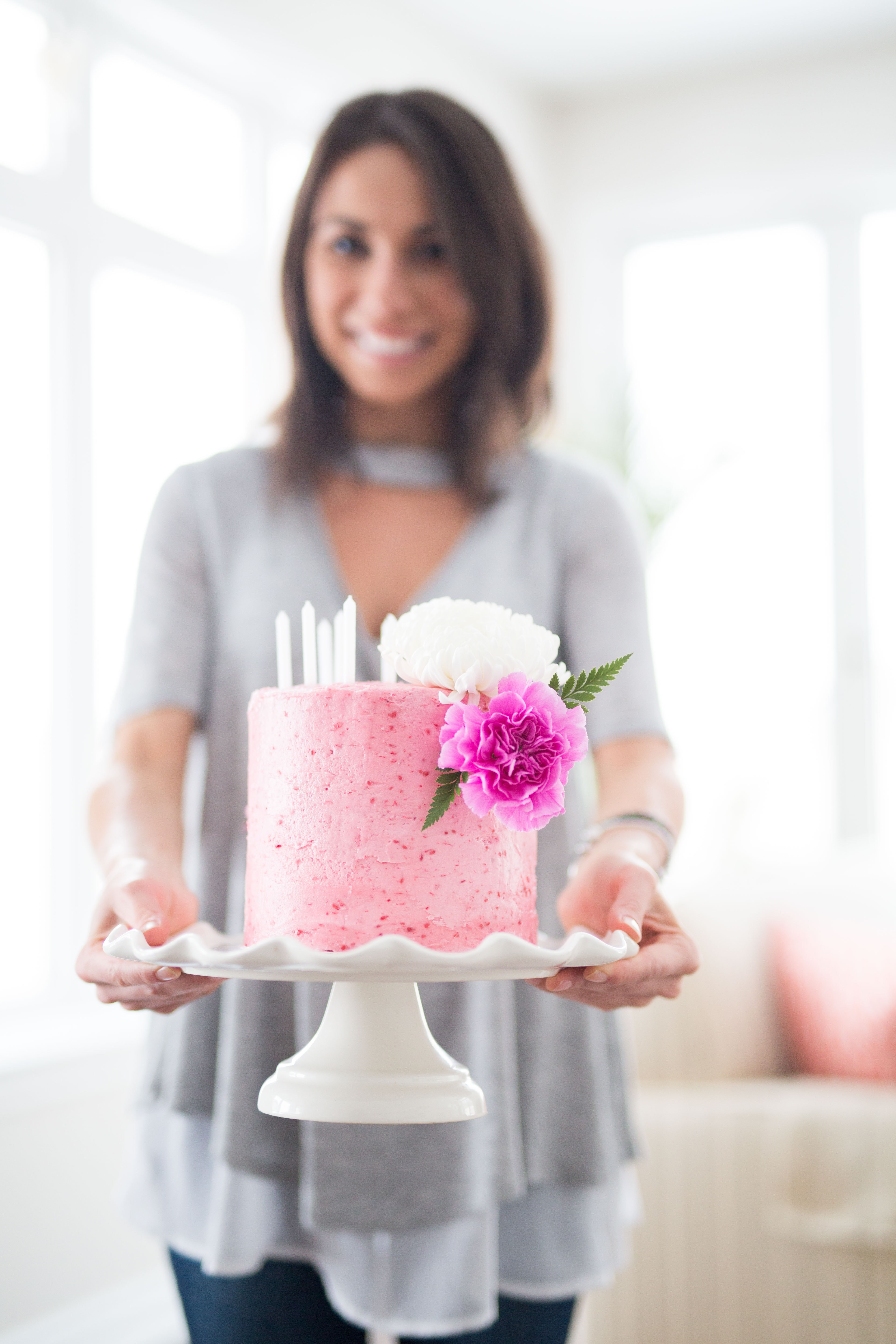 woman holding one layer of cake with stand