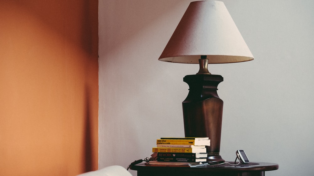 pile of books beside brown table lamp