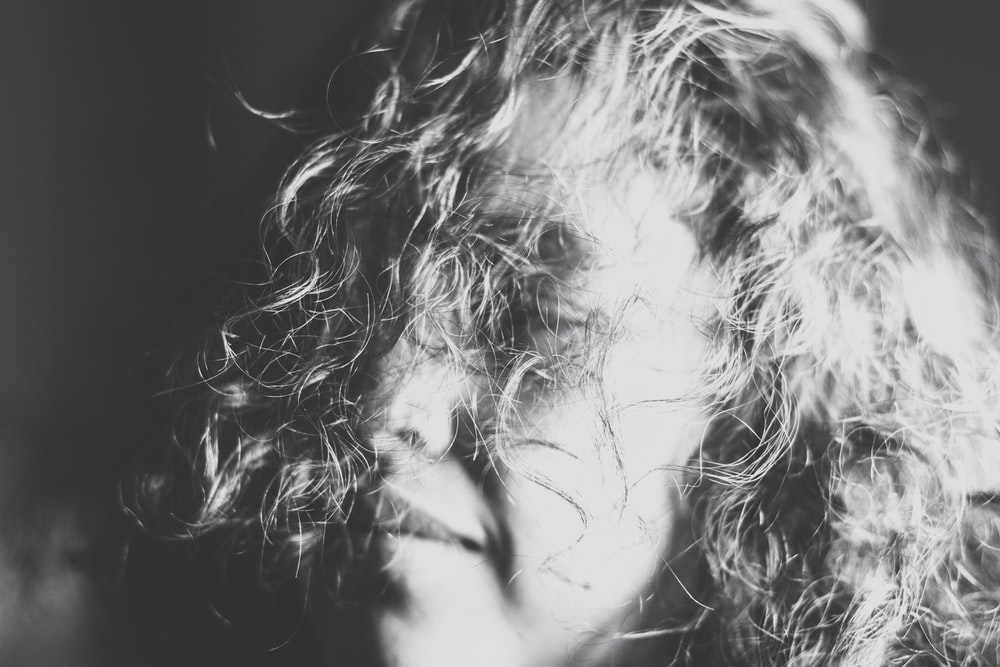 grayscale photography of a woman's face covered with her hair